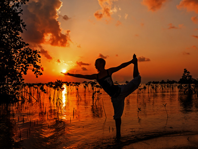 Young woman practicing yoga on the beach near mangroves